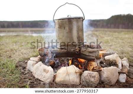 Cooking over a campfire - stock photo