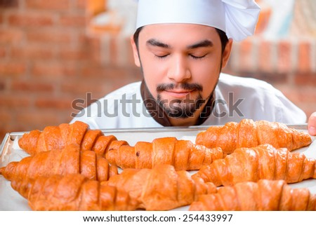 Cooking pastry. Cheerful young baker in apron smelling fresh baked croissants with closed eyes while standing on the background of a bakery shop - stock photo