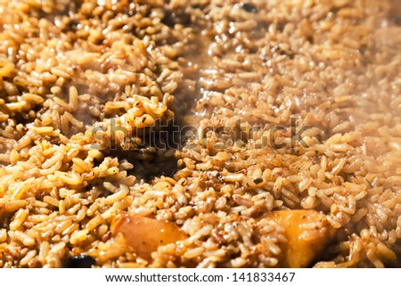 cooking pilaf with quince in outdoor cauldron close up - stock photo