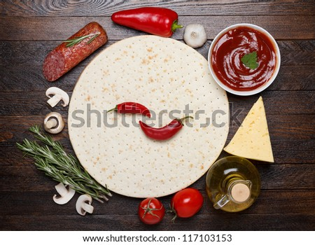 Cooking pizza with fresh ingredients - dough, salami, sauce, cheese, tomato, mushrooms, pepper - stock photo