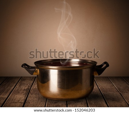 cooking pot on old wooden table - stock photo