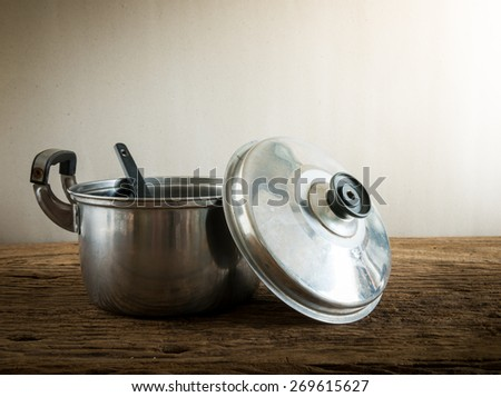 cooking pot on old wooden table with against grunge wall. vintage tone - stock photo