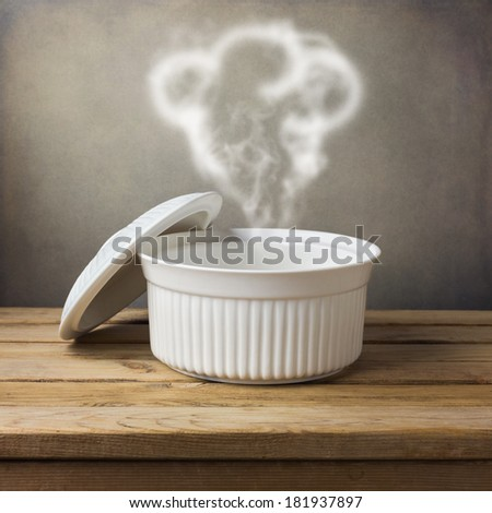 Cooking pot with steam as chef hat on wooden deck table over grunge background - stock photo