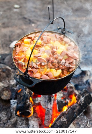 Cooking potatoes with sausages on a campfire - stock photo