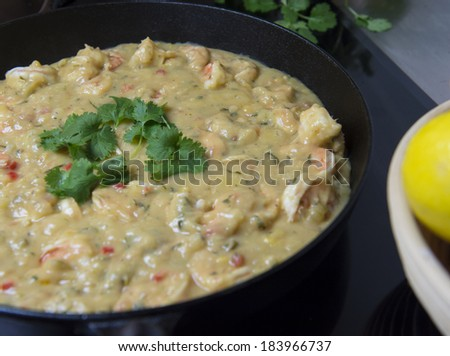 Cooking prawns with herbs in a frying pan - stock photo