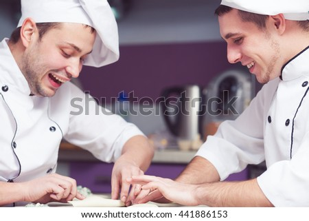 Cooking process concept. Smiling cooks in uniform putting filler of spinach and soft feta cheese on slice of puff pastry and making french chausson. Close up. Indoor shot - stock photo