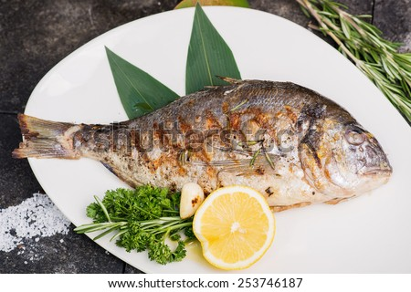 cooking process dorado fish grilled fried fish served on a white plate with lemon and herbs - stock photo