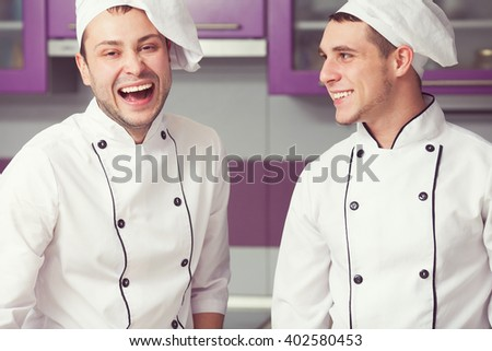 Cooking process, perfect teamwork concept. Portrait of two working men in cook uniform making food in modern kitchen. Indoor shot - stock photo