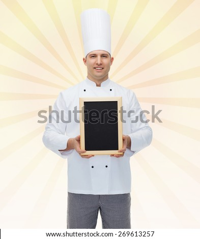 cooking, profession, advertisement and people concept - happy male chef cook showing and holding blank menu board over yellow burst rays background - stock photo