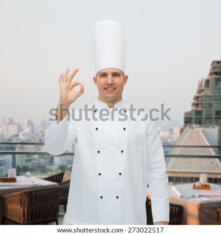 cooking, profession, gesture and people concept - happy male chef cook showing ok sign over city restaurant lounge background - stock photo
