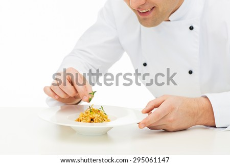 cooking, profession, haute cuisine, food and people concept - close up of happy male chef cook decorating dish - stock photo
