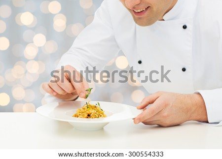 cooking, profession, haute cuisine, food and people concept - close up of happy male chef cook decorating dish over holidays lights background - stock photo