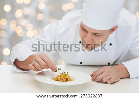 cooking, profession, haute cuisine, food and people concept - happy male chef cook decorating dish over christmas holidays lights background - stock photo