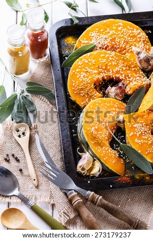 Cooking pumpkin with garlic, sage, sesame seed and spices. Close up image - stock photo