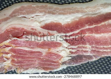 Cooking raw bacon on skillet - stock photo