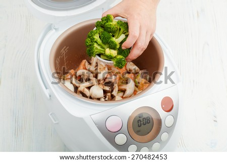 cooking salmon with mushrooms and broccoli in multicooker closeup - stock photo