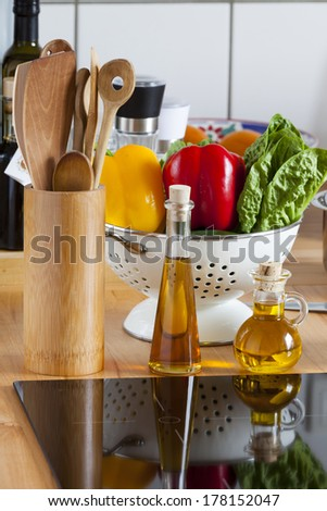 Cooking Spoon Rack, Vegetable, and Olive Oil on Worktop with Copy Space in lower and upper Area of the Image - stock photo