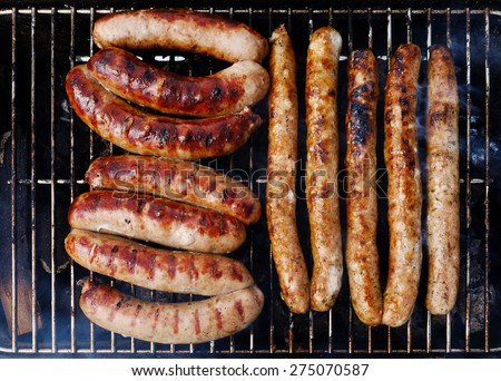 Cooking tasty sausages on the grill on flame. Flat lay food meat preparing. BBQ barbecue texture and meat background. - stock photo