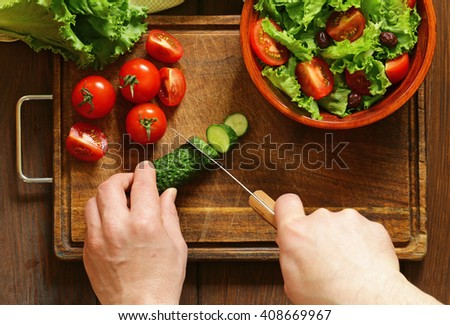 cooking vegetable salad (tomatoes, lettuce, cucumbers) on a wooden board, top view - stock photo