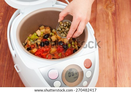 cooking vegetable stew with addition of capers in multicooker closeup - stock photo