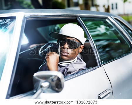 cool african man in old car - stock photo