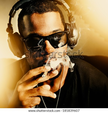 cool african man smoking joint wearing headphones - stock photo