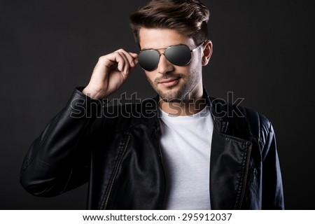 Cool and handsome. Handsome young man adjusting his sunglasses and looking at camera while standing against black background - stock photo