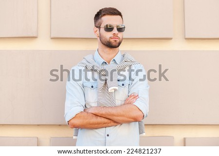 Cool and handsome. Handsome young man in sunglasses keeping arms crossed and looking away while standing in front of the textured wall outdoors - stock photo