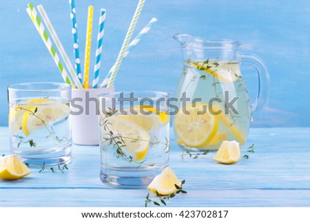 Cool beverage with lemon and thyme, on blue wooden background - stock photo