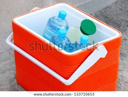 Cool box containing water bottles and juice - stock photo