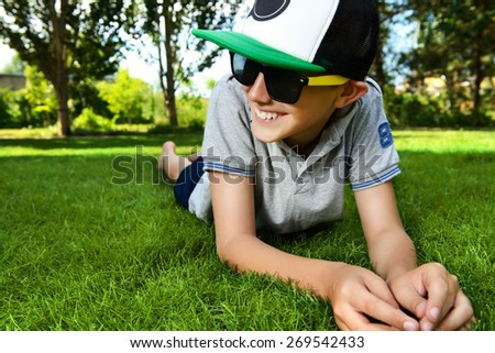 Cool boy lying on a grass at a park and smiles. Summer day. Holiday. - stock photo
