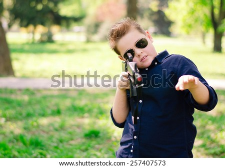 cool boy with a gun in the park - stock photo
