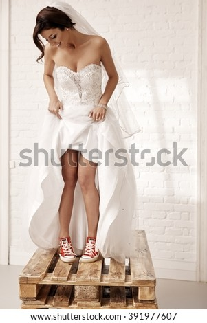 Cool bride standing on pallet in red sneakers and white wedding dress. - stock photo