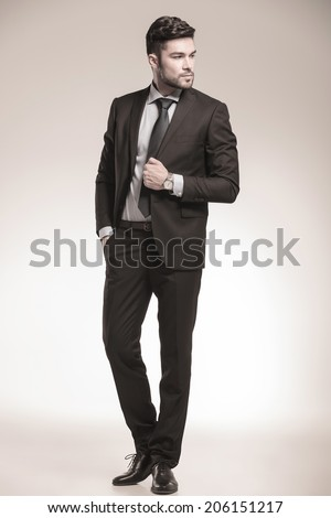 cool business man looking to his side , full body picture in studio - stock photo