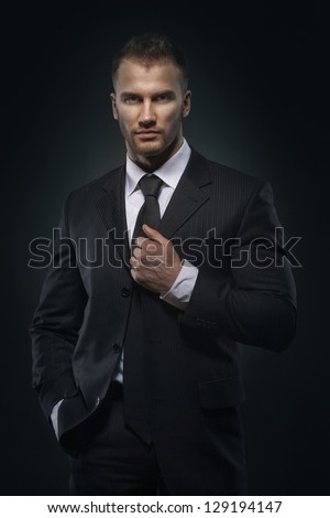 Cool businessman standing on dark gradient background - stock photo