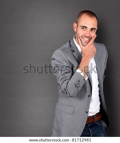 Cool businessman standing with hand on chin - stock photo