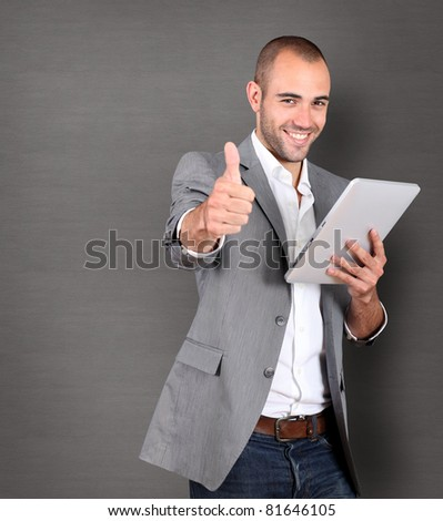 Cool businessman using touch pad on grey background - stock photo