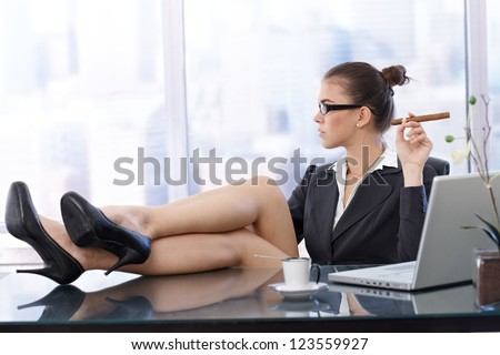 Cool businesswoman with feet up on desk, wearing high heels, having coffee, cigar handheld, side view in skyscraper office. - stock photo