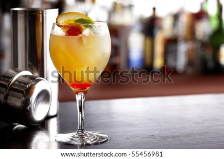 Cool, colorful summer drink with orange, lime and cherry, shot in bar with shaker - stock photo