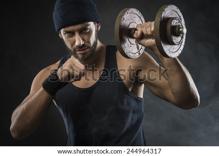 Cool confident man with cap lifting weights and working out - stock photo