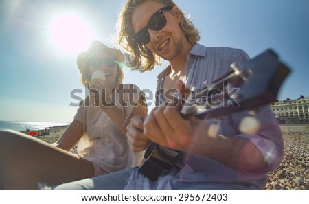 Cool couple on a beach having fun with a musical instrument and ice cream - stock photo