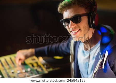 Cool dj smiling at camera at the nightclub - stock photo