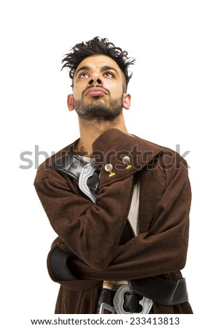 Cool Eastern European guy dressed in a brown pirate costume arms across his body looking up - stock photo