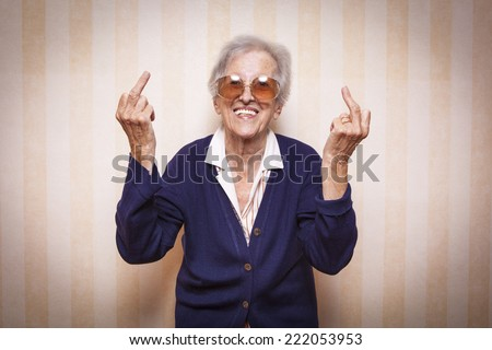 cool elder lady making middle finger sign - stock photo