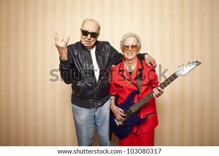 cool fashion elder couple with electric guitar - stock photo
