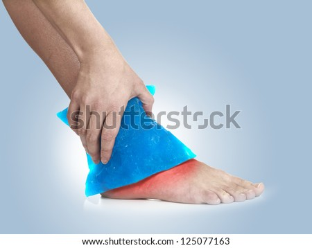 Cool gel pack on a swollen hurting ankle. Medical concept photo.  Color Enhanced skin with read spot indicating location of the pain. - stock photo