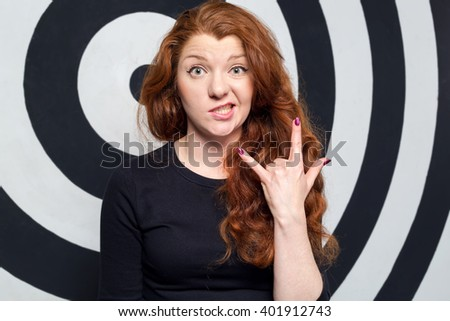 Cool gesture and fun woman. Handsome young woman gesturing and grimacing while standing against wall target background. Rock gestures. - stock photo