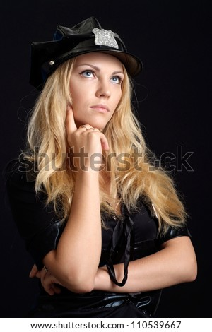 Cool girl in a uniform of  police officer on a black background - stock photo