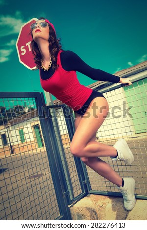 cool girl in street style posing on a fence - stock photo