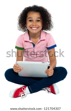 Cool girl kid sitting on the floor with wide grin on face holding tablet pc. - stock photo